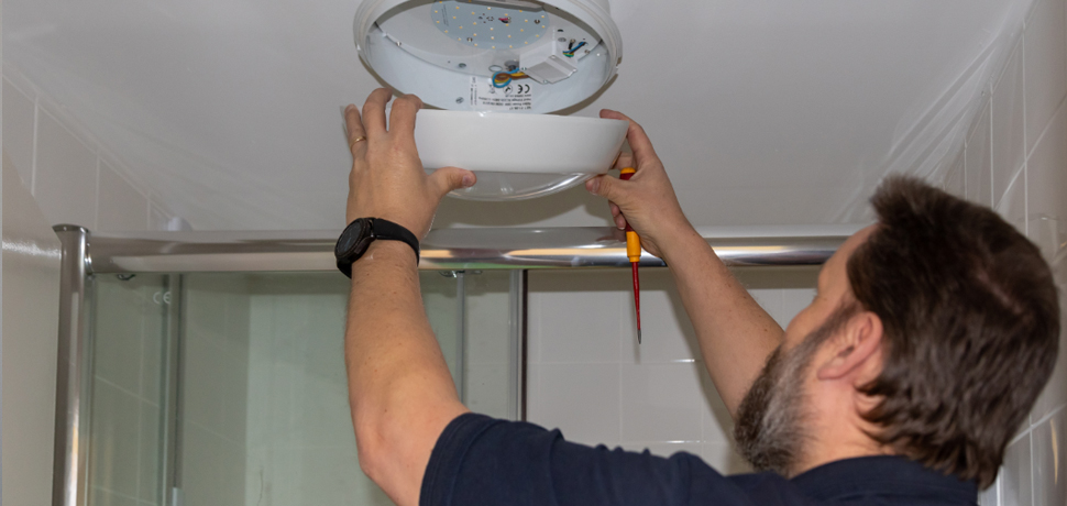 image: an Optivo team member fixing a light in a new bathroom