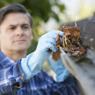 image: man cleaning guttering