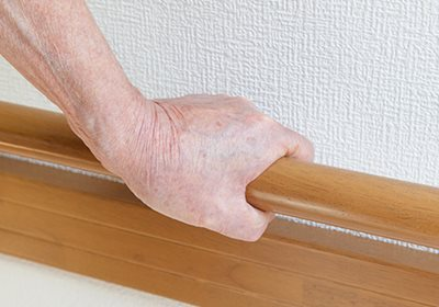 Image: A woman holding onto a hand rail in her home