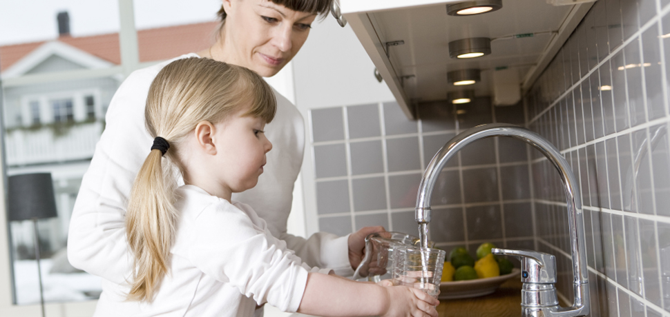 Image: mother and daughter filling glasses of water