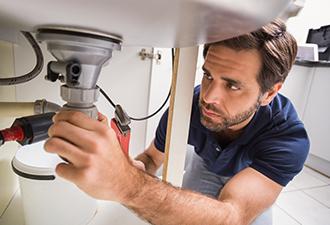 Image: A man checking pipes