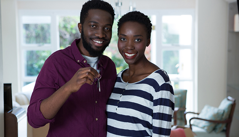 image: Smiling couple with the keys to their new home